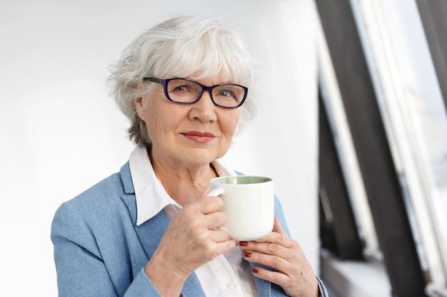 Erfolgreiche ordentliche kaukasische geschäftsfrau mittleren alters in formellen kleidern und brillen, die während der kaffeepause ruhe haben, tasse halten und mit selbstbewusstem glücklichem lächeln schauen. menschen und lebensstil