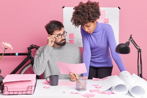 Erfolgreiche partnerschaftliche zusammenarbeit und teambuilding-konzept. beschäftigter männlicher chef und weibliche angestellte diskutieren über zukünftige architekturprojekte, tauschen erfahrungen miteinander aus und posieren im coworking space