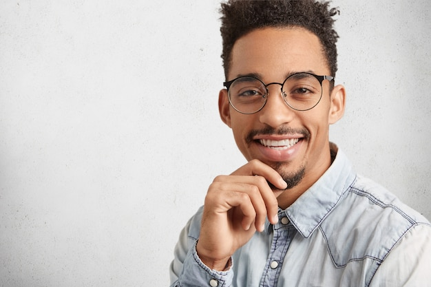 Erfolgreiche positive männliche arbeiter oder kreative person trägt stilvolle kleidung, hat ein spezifisches aussehen