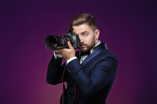 Erfolgreiche professionelle fotografen im smoking verwenden dslr-digitalkamera bei dunkelheit Premium Fotos
