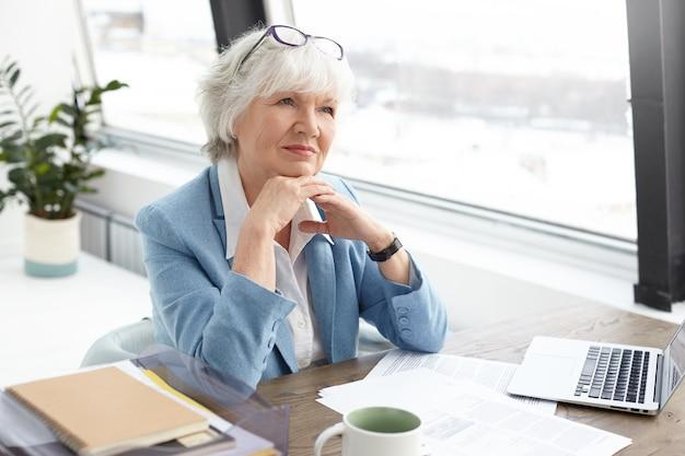 Erfolgreiche qualifizierte attraktive ältere herausgeberin des beliebten modemagazins, die an ihrem arbeitsplatz mit papieren, bechern und offenem tragbarem computer sitzt, hände faltet und nachdenklichen gesichtsausdruck hat