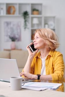Erfolgreiche reife agentin mit smartphone, die einen der kunden anruft, während sie am arbeitsplatz in der häuslichen umgebung sitzt