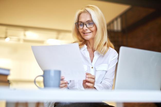 Erfolgreiche reife geschäftsfrau in gläsern, die mit laptop lächeln und papierkram im büro erledigen