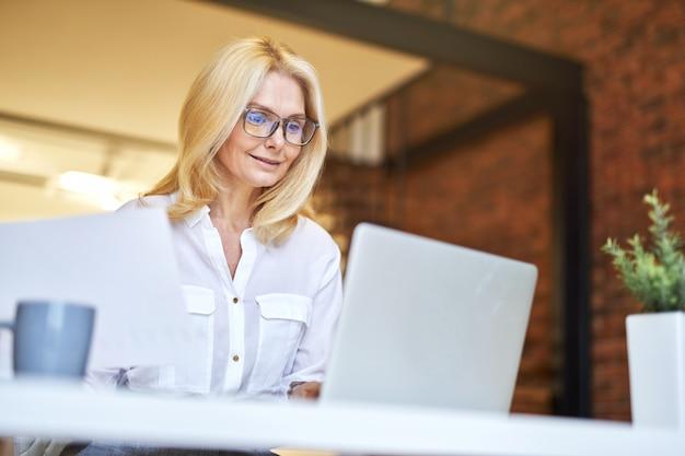 Erfolgreiche reife geschäftsfrau mit brille, die lächelt, während sie am laptop arbeitet und papierkram erledigt