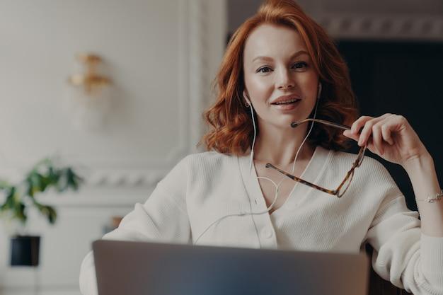 Erfolgreiche rothaarige unternehmerin bereit, online-verhandlungen mit kollegen zu führen