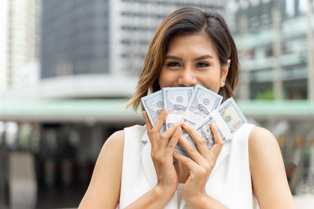 Erfolgreiche schöne asiatische geschäftsfrau, die geld us-dollar rechnungen hält