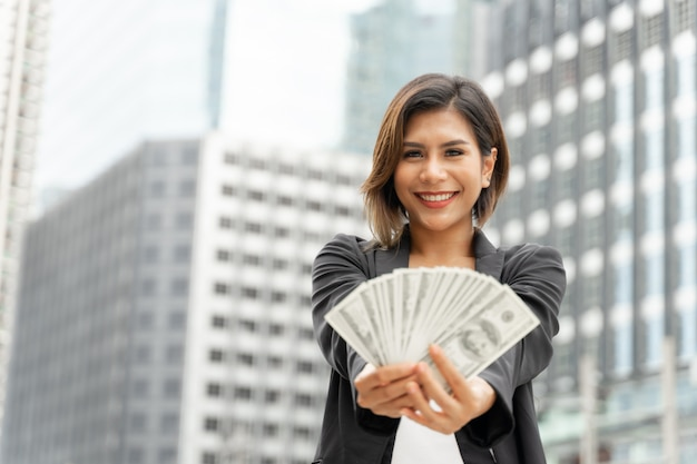 Erfolgreiche schöne asiatische geschäftsfrau, die in der hand geld us-dollar rechnungen, geschäftskonzept hält