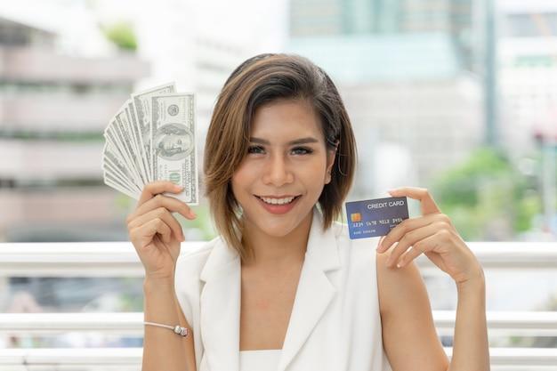 Erfolgreiche schöne asiatische geschäftsfrau, die in der hand geld us-dollar rechnungen und kreditkarte hält