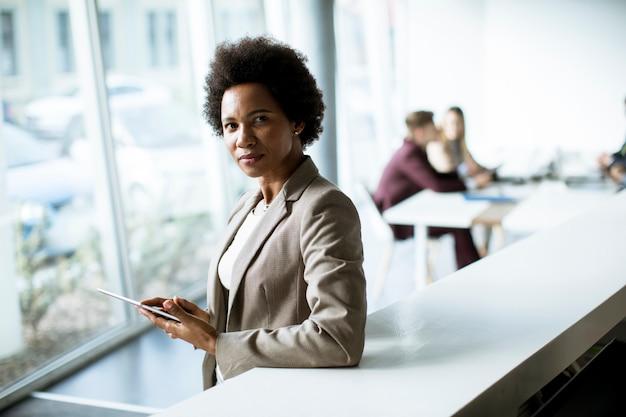 Erfolgreiche schwarze afroamerikanische geschäftsfrau, die mit digitalem tablett am modernen büro arbeitet