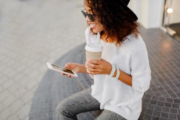 Erfolgreiche schwarze frau, bloggerin oder geschäftsleiterin, die handy während der kaffeepause verwendet.