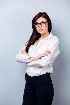 Erfolgreiche selbstbewusste junge frau mit brillen, die hände kreuzen