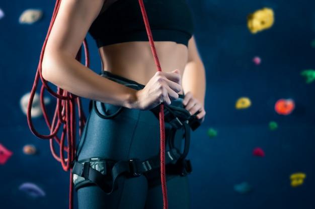 Erfolgreiche starke selbstbewusste sportfrau weiblicher alpinistenkletterer, der gegenüber wand bleibt