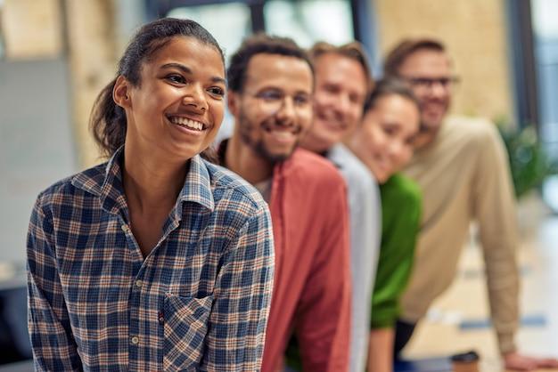 Erfolgreiche startup-teamgruppe junger glücklicher multiethnischer kollegen, die beim posieren in der lächeln