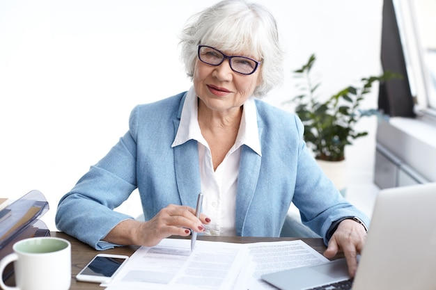 Erfolgreiche stilvolle reife weibliche geschäftsführerin, die brillen und formelle kleidung trägt, die durch finanzbericht schaut, am schreibtisch arbeitet, elektronische geräte verwendet und notizen macht