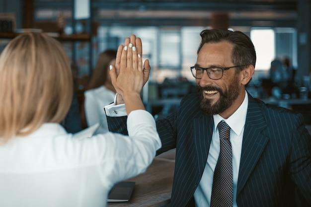 Erfolgreiche teamarbeit, die fröhlichen geschäftsmann in den brillen feiert, die hohe fünf mit der mitarbeiterin geben, die zurück im vordergrund steht. teamwork-konzept.