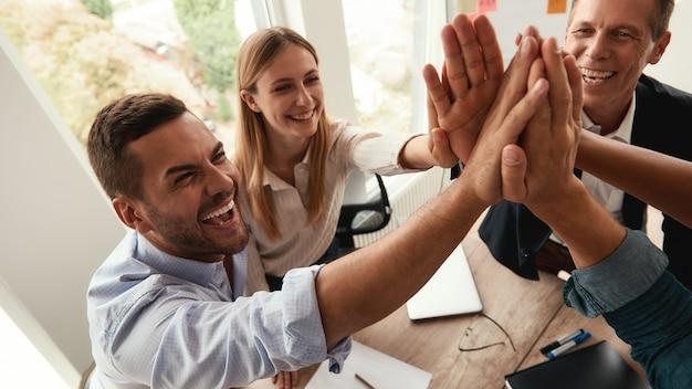 Erfolgreiche teamgeschäftsleute, die sich gegenseitig highfive geben und lächeln, während sie in der zusammenarbeit zusammenarbeiten