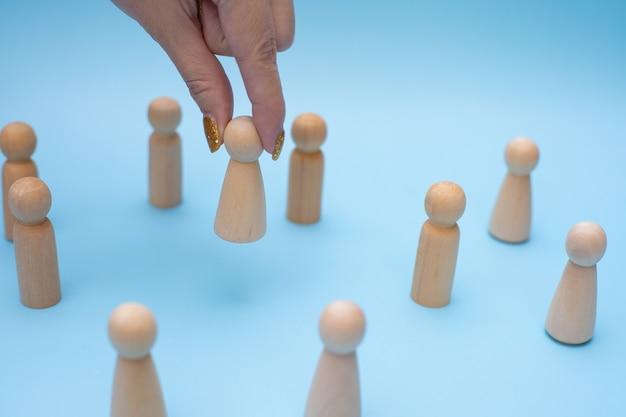 Erfolgreiche teamleiterin, frauenhand, wählt leute aus, die sich von den anderen abheben.