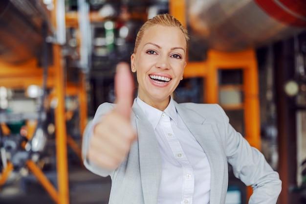 Erfolgreiche unabhängige geschäftsführerin mittleren alters im anzug, die im heizwerk steht und daumen hoch zeigt und in die kamera schaut.