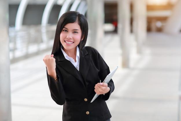 Erfolgreiche und glückliche geschäftsfrau, die tablette hält