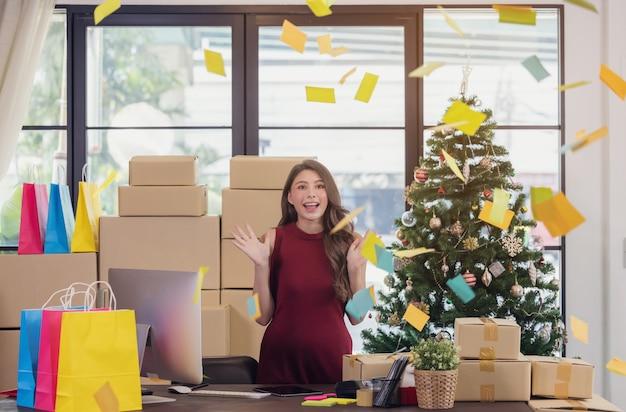 Erfolgreiche unternehmerin mit paketboxen in ihrem eigenen job online-shopping-geschäft zu hause, überraschender gewinner, der online gewinnt