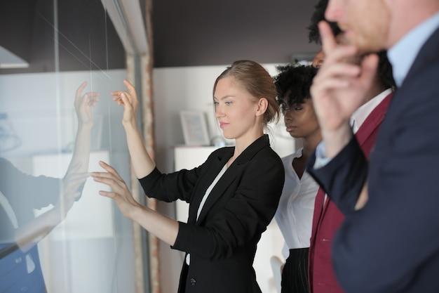 Erfolgreiche weibliche teamleiterin in einem formellen outfit, die das neue projekt multiethnischen partnern vorstellt