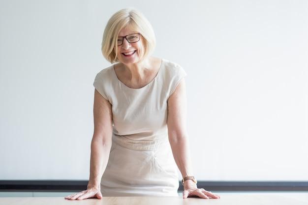 Erfolgreicher älterer weiblicher führer, der am tisch steht