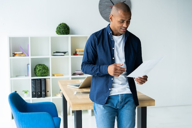 Erfolgreicher afrikanischer unternehmer, der dokumente mit aufmerksamem und konzentriertem blick studiert und kaffee im café trinkt. dunkelhäutiger geschäftsmann, der sich auf arbeitsfragen konzentriert und papiere für geschäftsabschlüsse unterschreibt