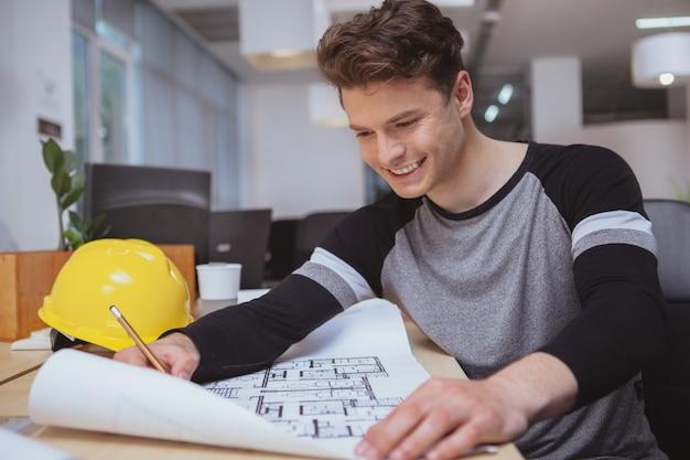 Erfolgreicher architekt, der an plänen im büro arbeitet