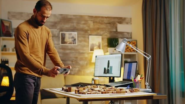 Erfolgreicher architekt, der mit seinem telefon von gebäudemodellen fotos macht.