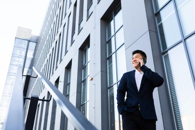 Erfolgreicher asiatischer geschäftsmann, der in der nähe des bürozentrums telefoniert und lächelt und glücklich wegschaut