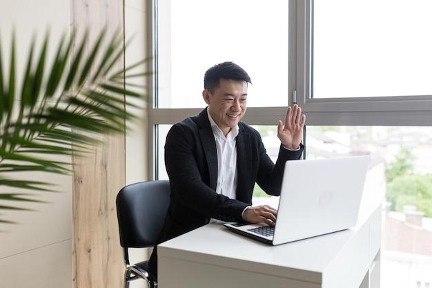 Erfolgreicher asiatischer geschäftsmann in einem schwarzen anzug arbeitet an einem laptop in einem stylischen büro