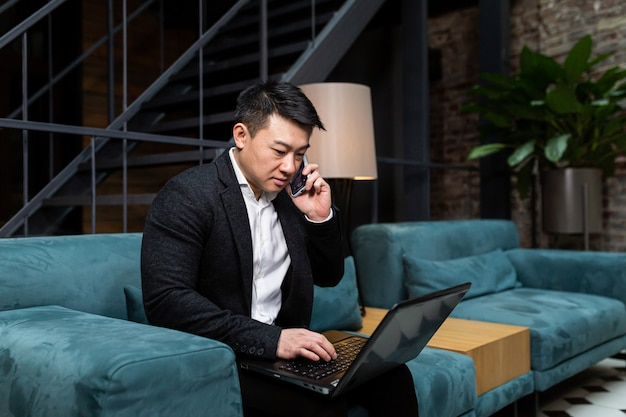 Erfolgreicher asiatischer geschäftsmann in einem schwarzen geschäftsanzug nutzt das telefon für videoanrufe und konferenzen, die in einem restaurant entspannen