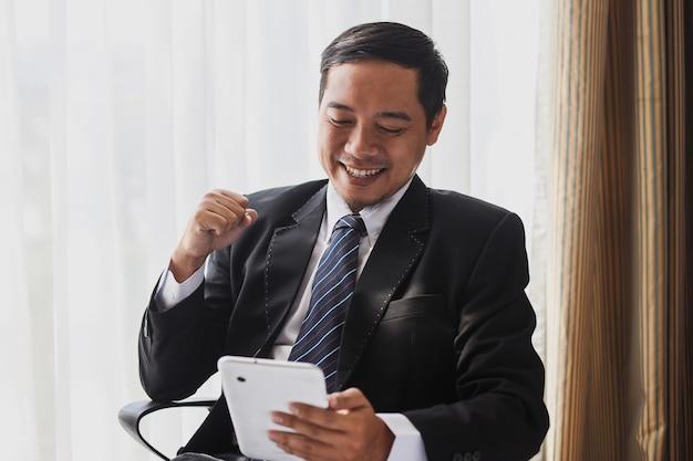 Erfolgreicher asiatischer geschäftsmann in schwarzem anzug und krawatte bekommt gute nachrichten vom smartphone