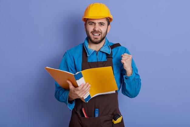 Erfolgreicher attraktiver kaukasischer mannarchitekt, geballte fäuste, während gelber papierordner in den händen gehalten wird, mit glücklichem ausdruck