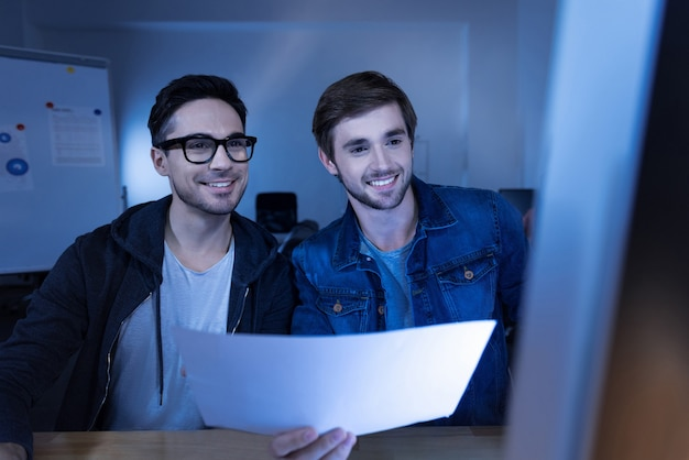 Erfolgreicher betrug. fröhliche, kluge, gutaussehende hacker, die lächeln und auf den computerbildschirm schauen, während sie beobachten, wie gestohlenes geld auf ihre konten fließt
