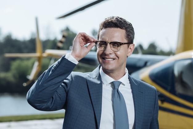 Erfolgreicher ceo. die nahaufnahme eines gutaussehenden jungen ceo, der seine brille justiert und an einem hubschrauberlandeplatz für die kamera posiert