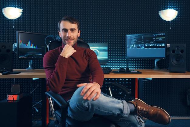 Erfolgreicher designer oder herausgeber, der bein über bein in einem ledersessel sitzt, der zur kamera schaut, mit monitoren und schallschutzwand im hintergrund mit kopierraum