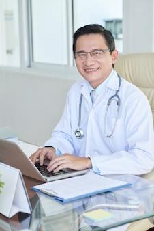 Erfolgreicher doktor, der im büro arbeitet