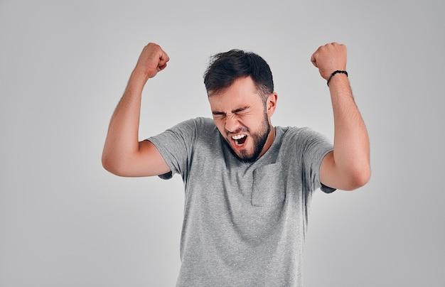 Erfolgreicher emotionaler junger kaukasischer männlicher sportler mit dunklem haar, das ja schreit und geballte fäuste in die luft hebt und sich aufgeregt fühlt. menschen, erfolg, triumph, sieg, sieg und feier