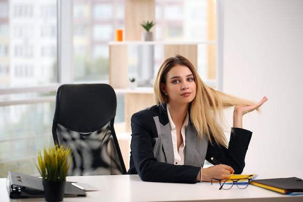 Erfolgreicher, entspannter, verträumter geschäftsfrauenanwalt, der an ihrem arbeitsplatz ruht.