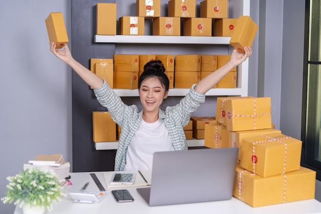 Erfolgreicher frauenunternehmer mit paketkästen in ihrem eigenen job, der onlinegeschäft kauft