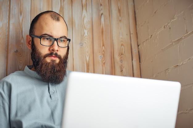 Erfolgreicher freiberuflicher mann des lebensstils mit bart erzielt neues ziel mit laptop im dachbodeninnenraum