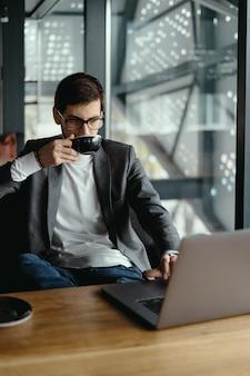 Erfolgreicher geschäftsmann, der am laptop beim kaffeetrinken arbeitet