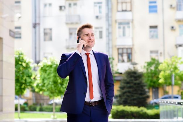 Erfolgreicher geschäftsmann, der am telefon spricht und lächelt.