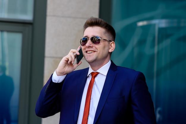 Erfolgreicher geschäftsmann, der am telefon spricht.