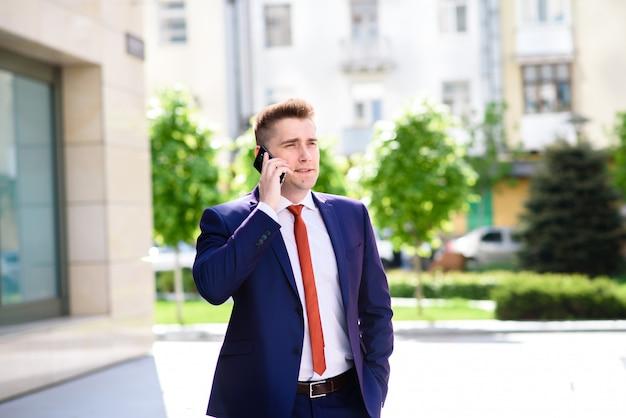 Erfolgreicher geschäftsmann, der am telefon und am lächeln spricht.