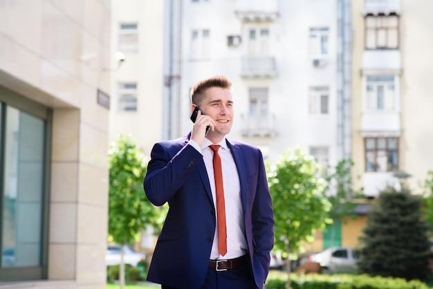 Erfolgreicher geschäftsmann, der am telefon und dem lächeln spricht.