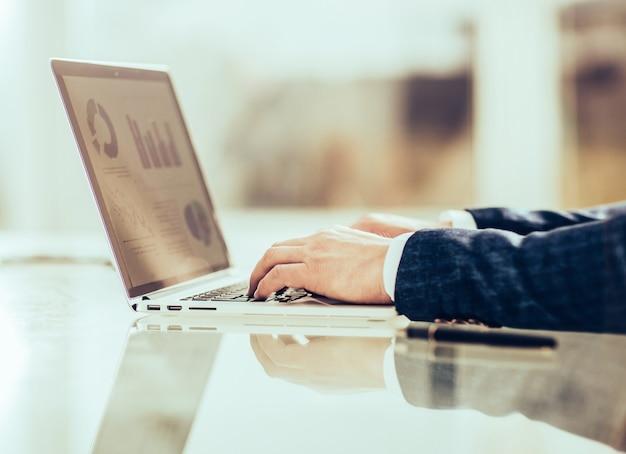 Erfolgreicher geschäftsmann, der an laptop mit finanzdaten arbeitet.
