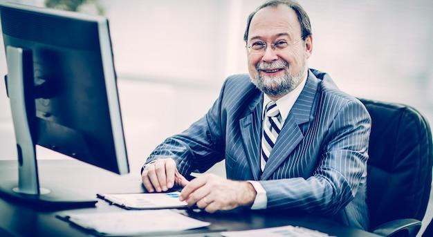 Erfolgreicher geschäftsmann, der bei der arbeit mit finanzdiagrammen arbeitet