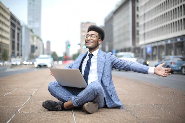 Erfolgreicher geschäftsmann, der beim arbeiten mit seinem laptop in der straße gut sich fühlt